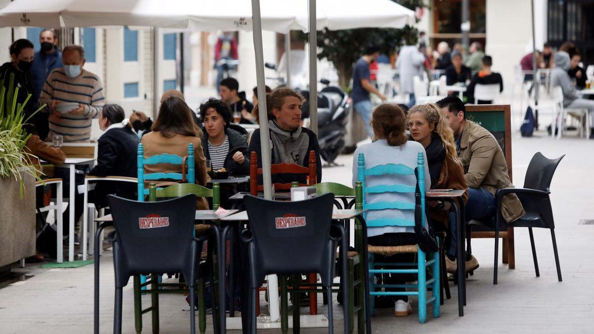 Varias personas disfrutan en la terraza de un bar