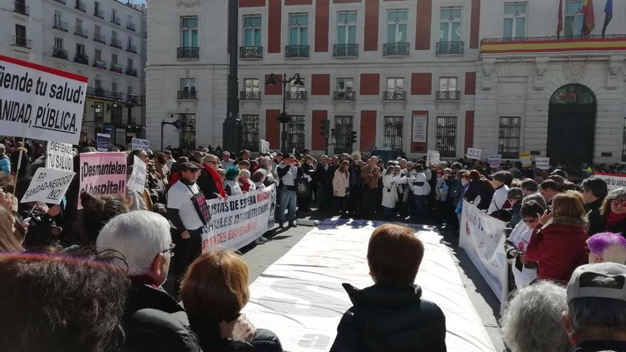 Manifestantes de la Marea Blanca leyendo un manifiesto en frente de la sede de la Comunidad de Madrid