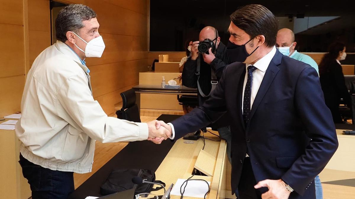 El procurador de Por Ávila, Pedro Pascual, saluda al consejero de Fomento y Medio Ambiente, Juan Carlos Suárez Quiñones, antes de su comparecencia para explicar la gestión del incendio de Navalacruz.