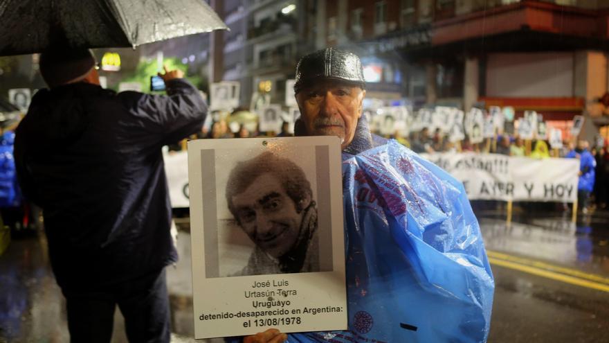 Un hombre muestra un cartel con la foto de un desaparecido durante la vigésimo cuarta edición de la Marcha del Silencio, exigiendo justicia por los detenidos desaparecidos durante la dictadura cívico militar del país (1973-1985)