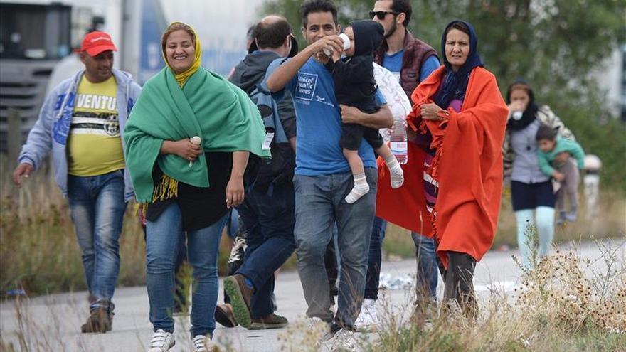 Refugiados cruzan la frontera por la localidad austríaca de Nickelsdorf este sábado tras salir de Hungría/ EFe