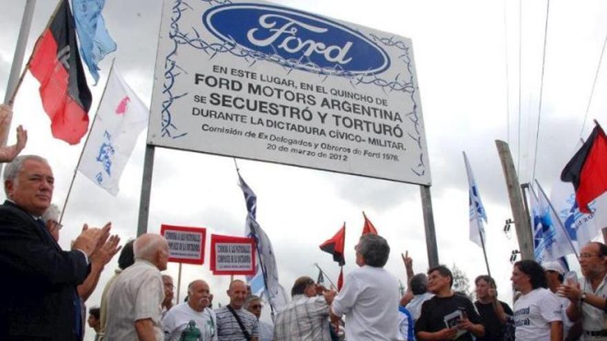 Militantes de izquierda y sobrevivientes del centro de detención en la planta de Ford en General Pachecho -Buenos Aires- levantan un cartel alusivo a las detenciones y torturas en la fábrica durante la dictadura militar. Cedida