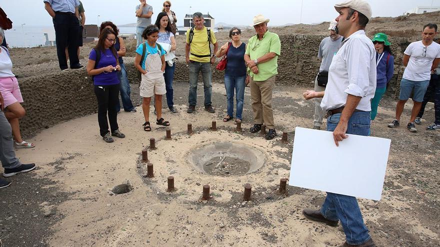 El historiador Artemi Alejandro muestra la batería de Taliarte a un grupo de asistentes