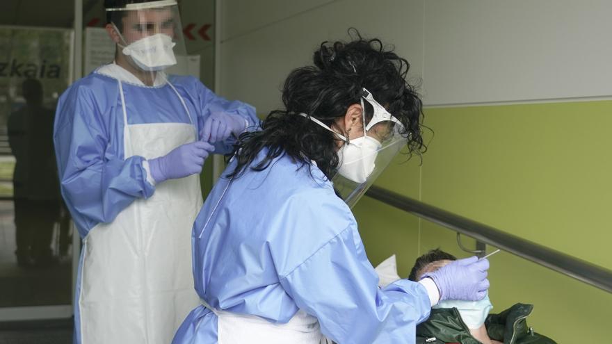 Archivo - Dos sanitarios protegidos con guantes, mascarillas y pantallas protectoras realizar una PCR , en Bilbao/Bizkaia/Euskadi (España) a 14 de abril de 2020.