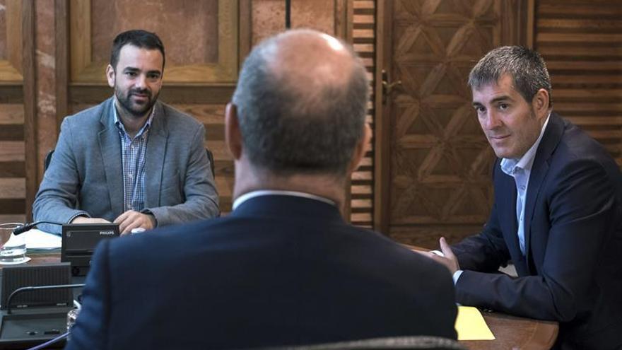 El presidente del Gobierno de Canarias, Fernando Clavijo (d) y el consejero de Presidencia, Aarón Afonso (i), charlan con el consejero canario de Economía, Industria, Comercio y Conocimiento, Pedro Ortega. (Efe/Ángel Medina G.).