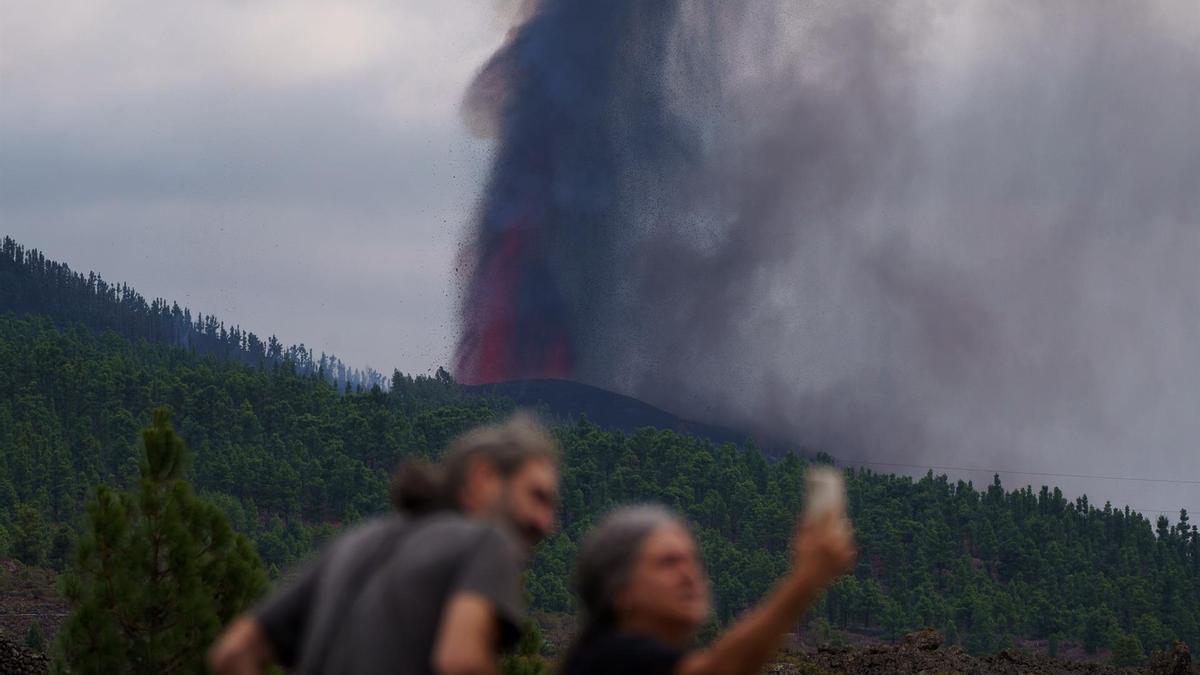 Dos vecinos fotografían la erupción del volcán de La Palma. (EFE)