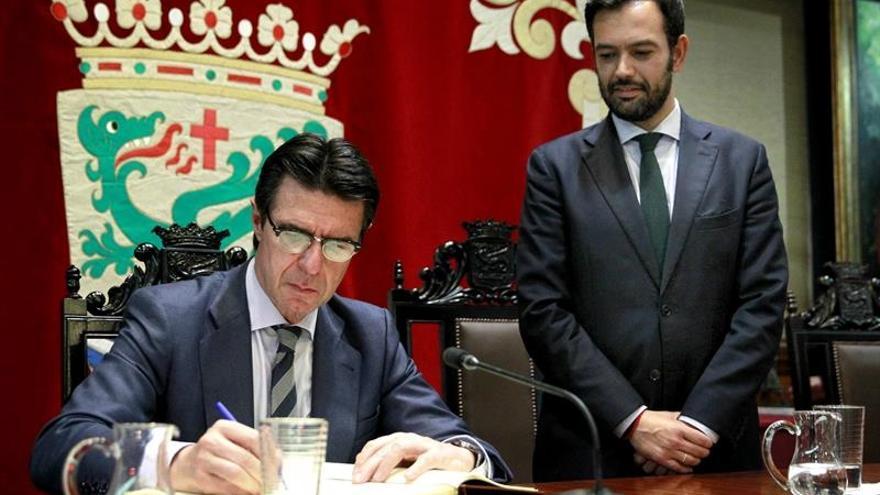 El ministro José Manuel Soria firma en el libro de honor durante su visita a Puerto de la Cruz, acompañado por el alcalde, Lope Afonso / Cristóbal García/EFE