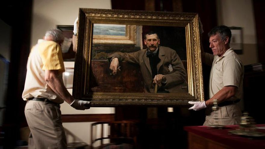 Dos operarios transportan el conocido retrato que Joaquín Sorolla pintó de Benito Pérez Galdós