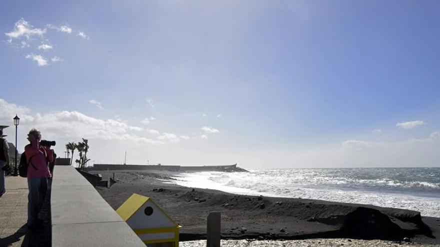 Una turista toma fotos al oleaje en la playa turística de Tazacorte, en la isla de La Palma. EFE/Miguel Calero