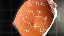 """El dibujo de un cerdo con la inscripción """"Júpiter"""", todo ello centrado en una pieza rota"""