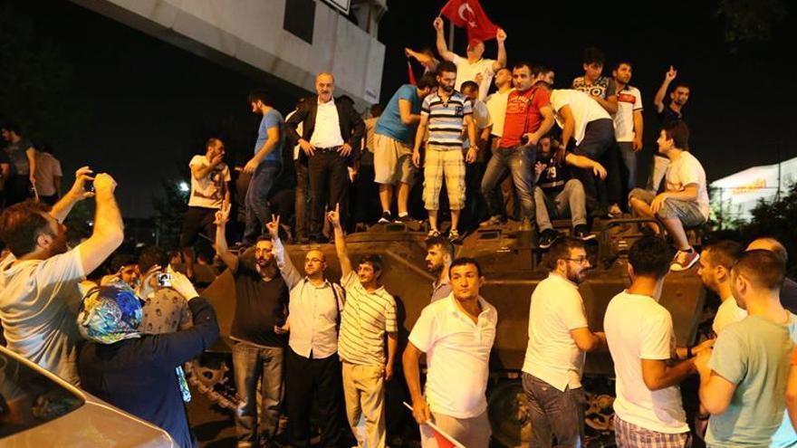 Numerosos ciudadanos turcos se suben a un tanque y ondean banderas tras fracasar el golpe militar en Estambul (Turquía).