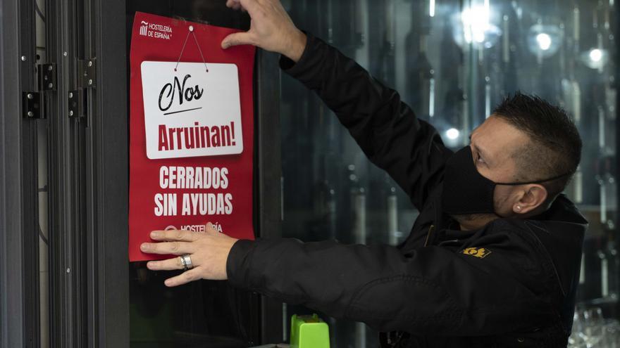 """Un trabajador de hostelería coloca un cartel donde se lee """"Nos arruinan. Cerrados sin ayudas"""", durante el primer día de reapertura de la hostelería en Logroño (España)."""