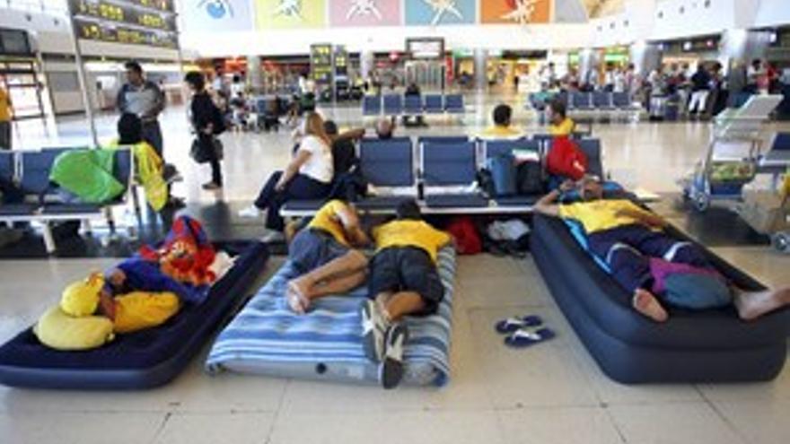 Dos de los trabajadores en huelga de hambre descansan en el suelo del aeródromo grancanario. (ACFI PRESS)