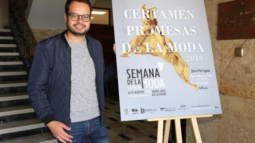 Jordi Pérez, consejero de Promoción Económica del Cabildo de La Palma posa junto al cartel oficial del Certamen.