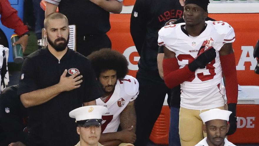 El quarterback de los San Francisco 49ers, Colin Kaepernick, se arrodilla en lugar de escuchar en pie el himno de EEUU antes de un partido en San Diego.
