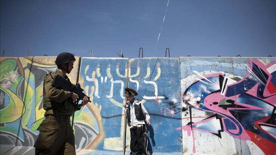 Un policía fronterizo israelí camina junto a un joven judío vestido como vaquero, en el muro que separa las zonas judía y musulmana de Hebrón, Cisjordania.