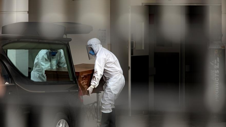 Trabajadores mueven un ataúd, el 22 de mayo de 2020, en el Hospital de Lima Este-Vitarte, en Lima (Perú).