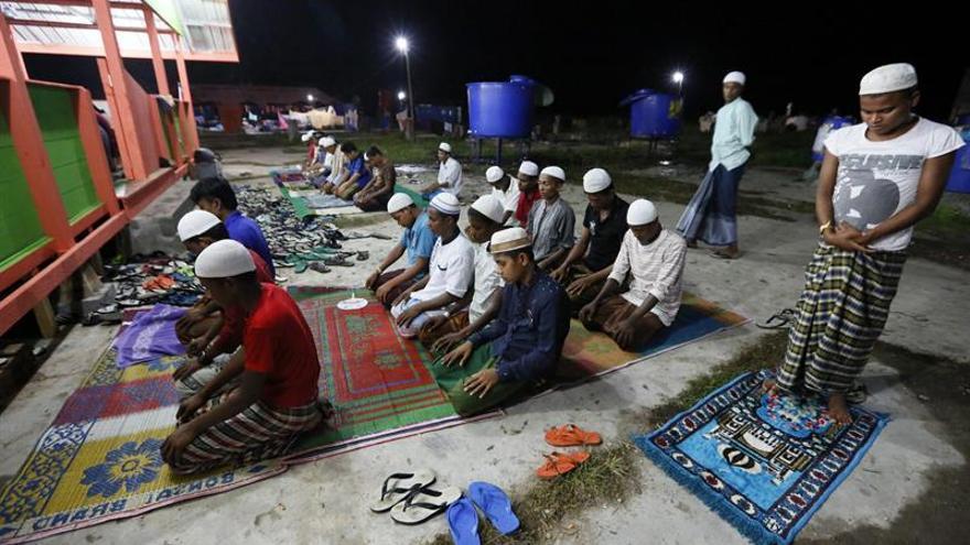 Musulmanes migrantes rohingya asisten a las oraciones de la mañana
