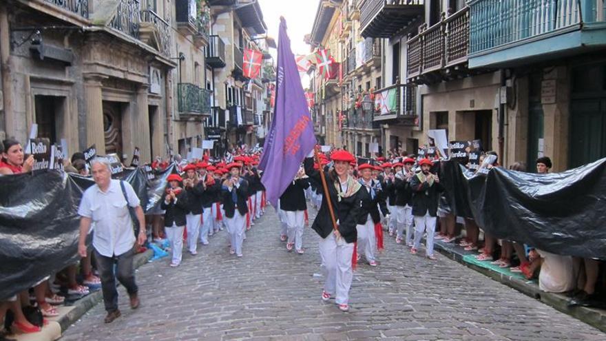 El alarde mixto desfila entre los plásticos negros colocados los partidarios del desfile tradicional