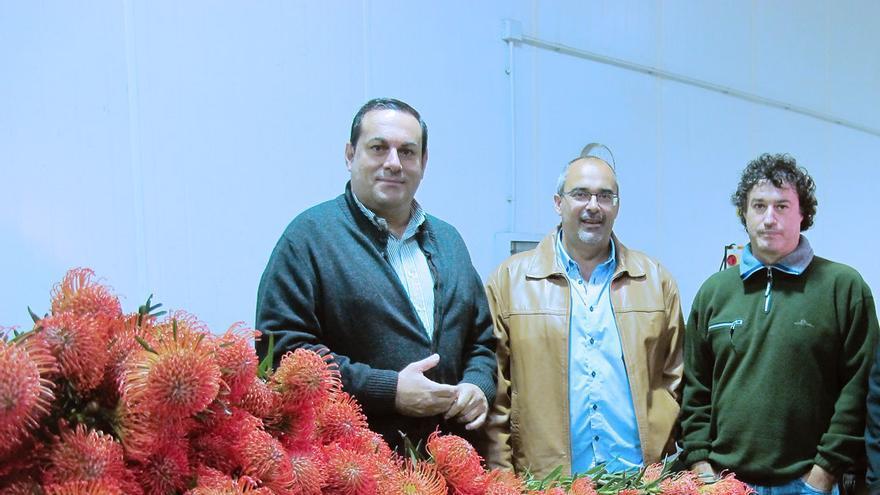 Basilio Pérez (i) junto a flores de protea.