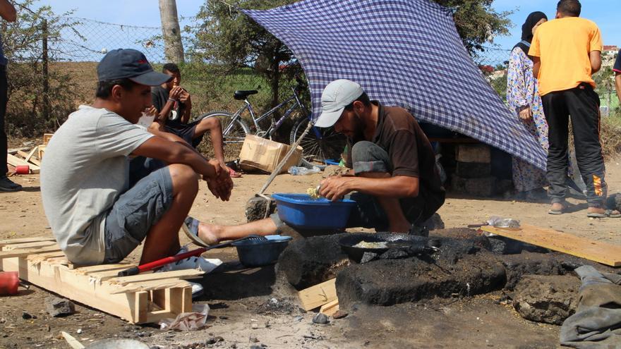 Varios refugiados sirios cocinan frente al CETI de Melilla.   Gabriela Sánchez.