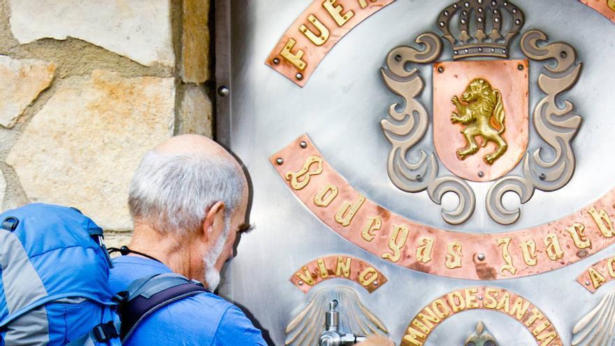 Un peregrino se refresca en la Fuente del Vino, junto a las Bodegas Iratxe. VIAJAR AHORA
