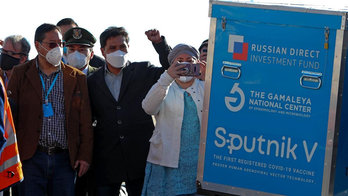 El presidente de Bolivia Luis Arce (i) observa un contenedor con dosis de la vacuna rusa Sputnik V en el Aeropuerto Internacional de El Alto (Bolivia). EFE/Martin Alipaz
