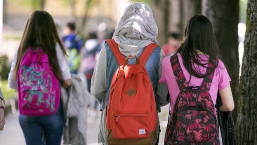 Tres menores, una de ellas con un 'hiyab', acuden a su centro educativo.