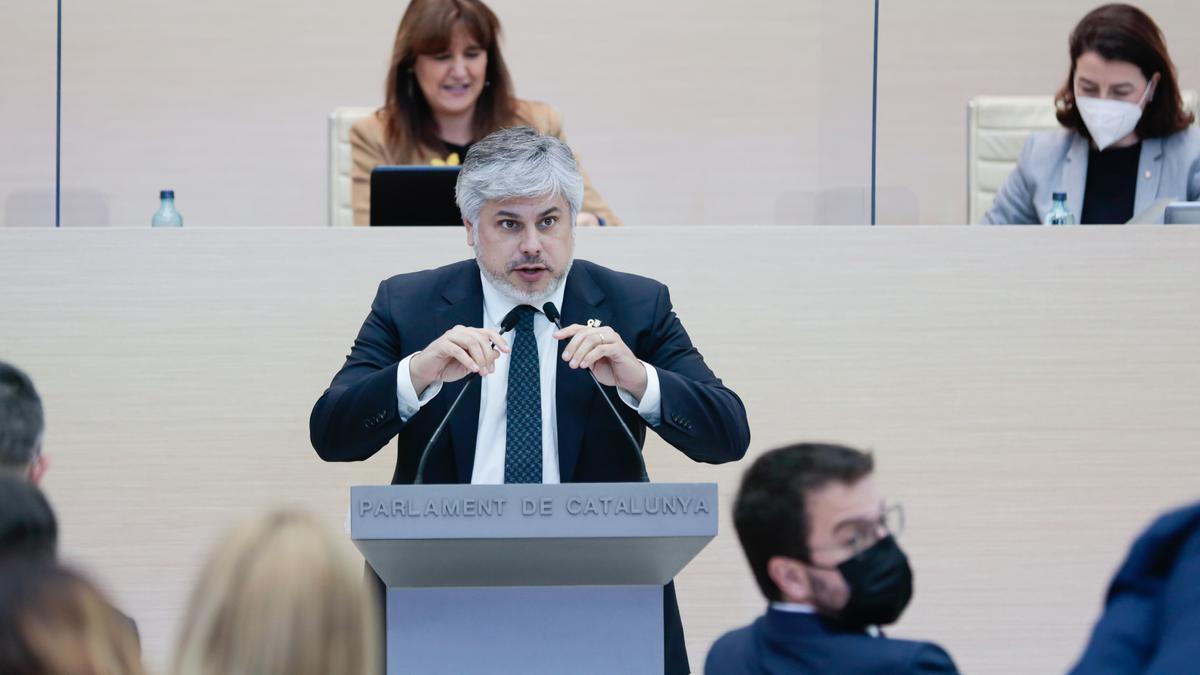 El portavoz de Junts, Albert Batet, interviene desde el atril mientras el candidato Pere Aragonès se gira para mirar hacia atrás