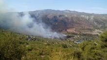 Un avión trabaja en las tareas de extinción del fuego en la Vall de la Gallinera