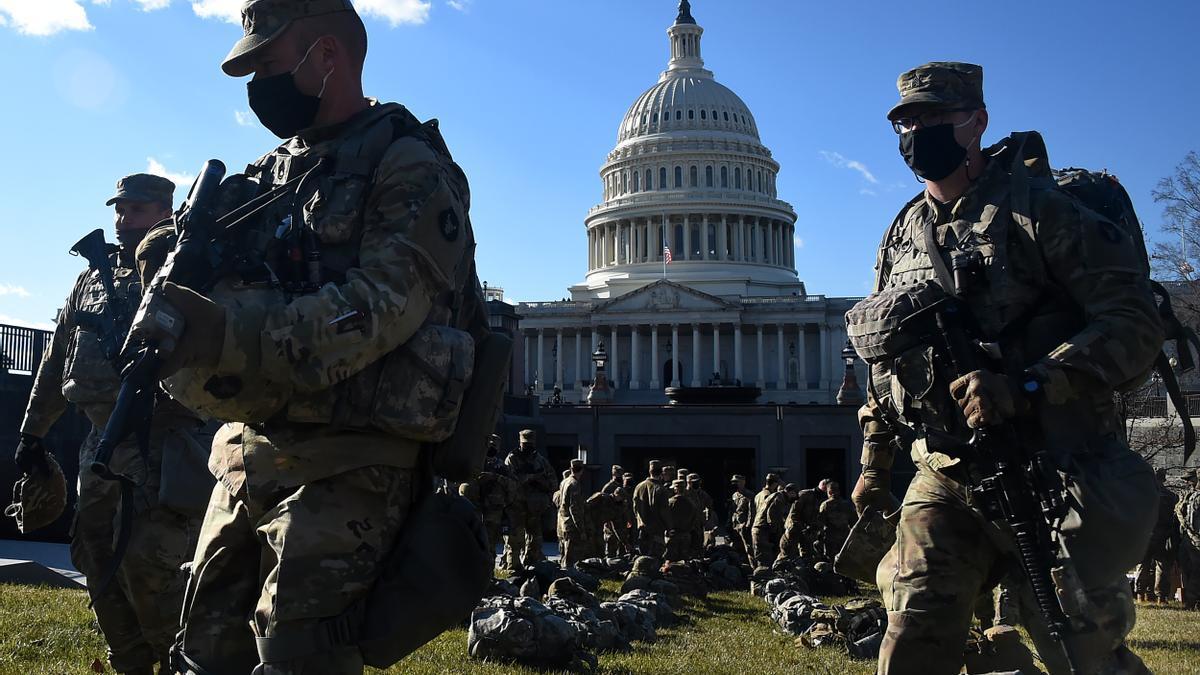Parte de los 25.000 efectivos de la Guardia Nacional transitan el parque National Mall, frente al Capitolio