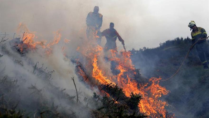 Efectivos del servicio de Bomberos durante las labores de extinción del incendio producido en la parroquia de Cures, Boiro (A Coruña, Galicia), en la Sierra del Barbanza.