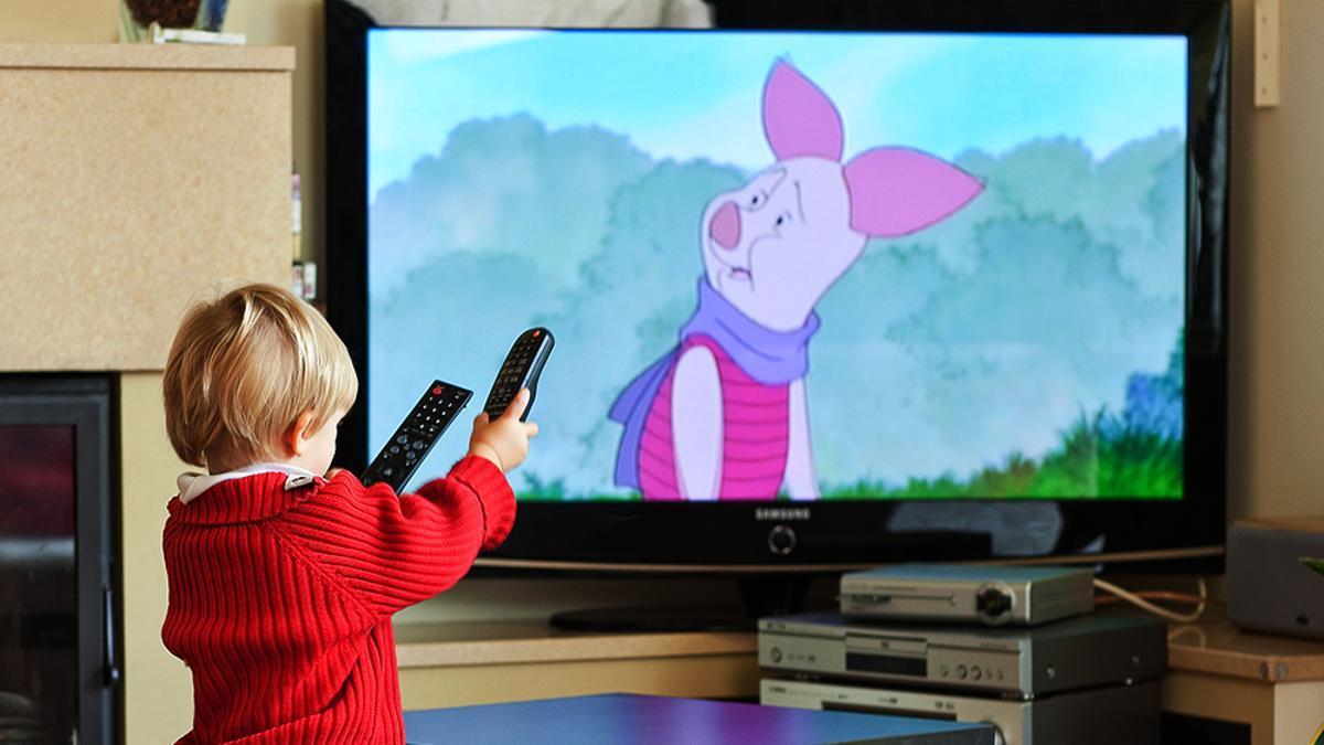 Un niño, a su aire con el mando a distancia del televisor