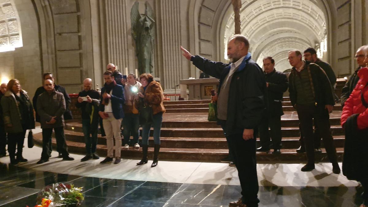 Un grupo de personas frente a las losas que han reemplazado la lápida de Franco. Uno de ellos hace el saludo franquista.