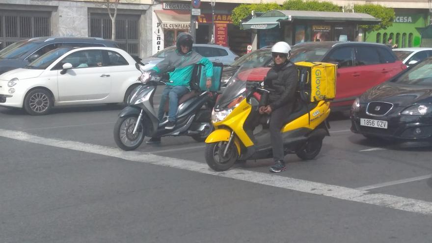 Repartidores de Glovo y Deliveroo en una calle de Murcia