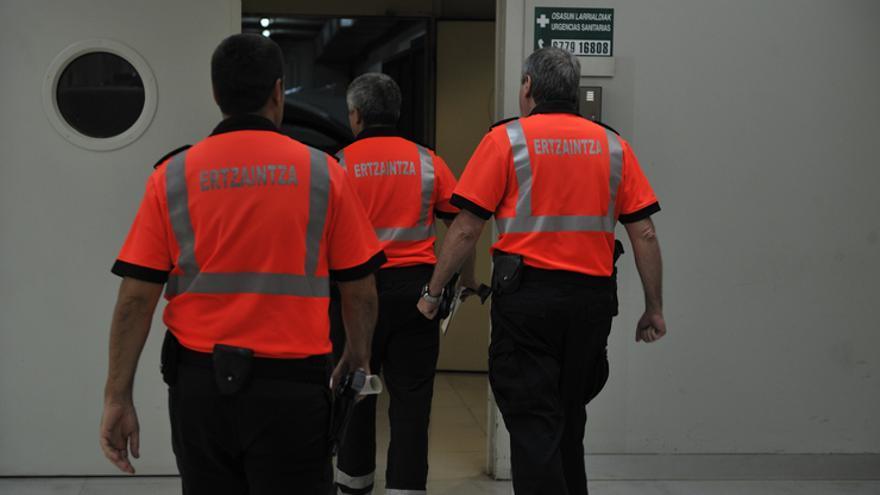 Tres ertzainas (ajenos a la información) en una comisaría