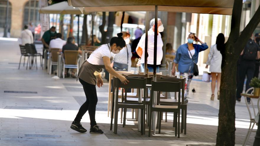 Una camarera con mascarilla prepara una terraza en la calle Ribera de València