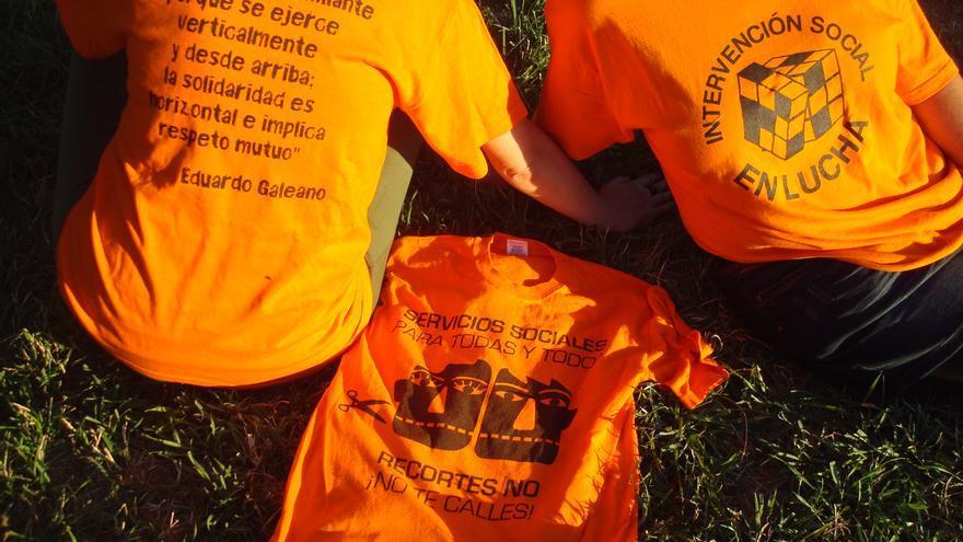 Las educadoras sociales entrevistadas, con la camiseta naranja en contra de los recortes y una cita de Eduardo Galeano