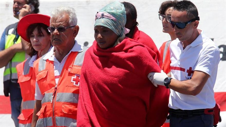 Un voluntario de Cruz Roja atiende en el muelle a algunos inmigrantes rescatados la semana pasada en el sur de Gran Canaria.