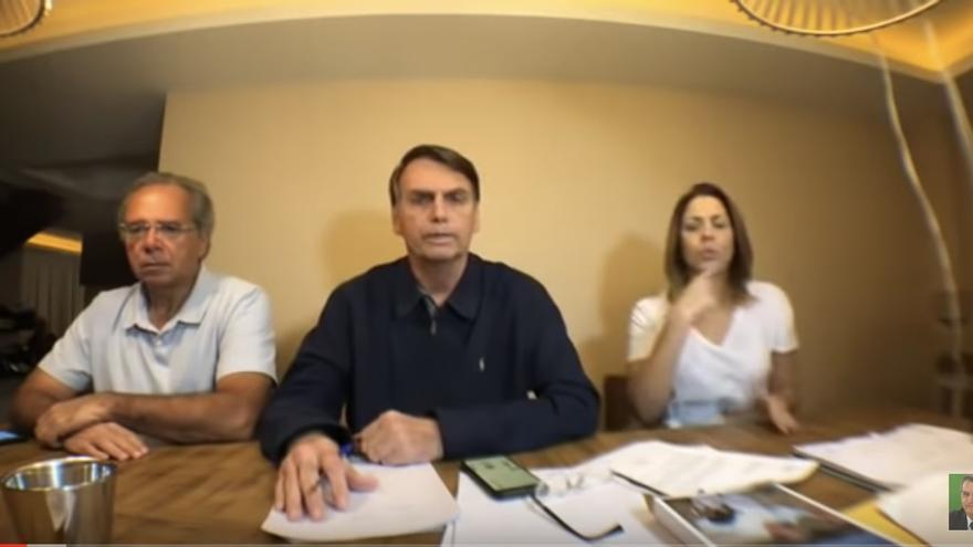 Bolsonaro y dos miembros de su equipo en el Facebook Live que hicieron tras conocerse los resultados de la primera vuelta de las elecciones presidenciales de Brasil.