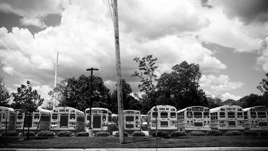 """Autobuses escolares esperan cerca de la High School de Brentwood, con un alto porcentaje de centroamericanos (dades?). Muchos de los jóvenes recién llegados a la escuela se unen a las pandillas. Carlos Argueta, ex pandillero y trabajador social en un high school de Long Island lo explica así: """"Algunos vienen y solo han estudiado allá tercero o cuarto grado. Otros vienen preparados, y los ponemos a todos juntos en el mismo salón de ESL (Inglés como Segunda Lengua). Se unen (a las pandillas) por protección, para tener amistades y novias. Pero el mayor problema es que los hemos puesto en un solo cuarto a todos estos jóvenes con tanto trauma, y los hemos puesto en un solo cuarto donde toda la frustración que cargan se la desquitan entre ellos."""""""