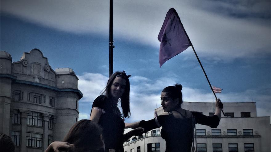 Una joven, con una bandera morada, en la manifestación del centro de Bilbao