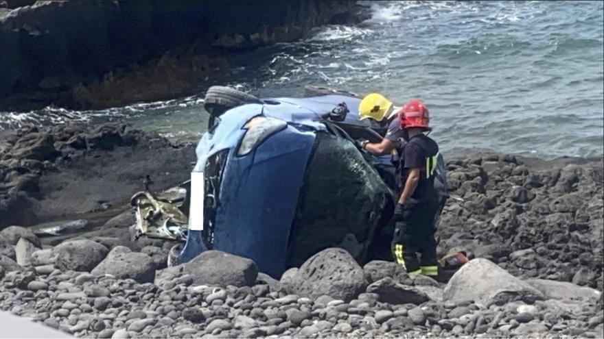 Dos bomberos junto al coche accidentado en la carretera de Puerto Naos a El Remo.
