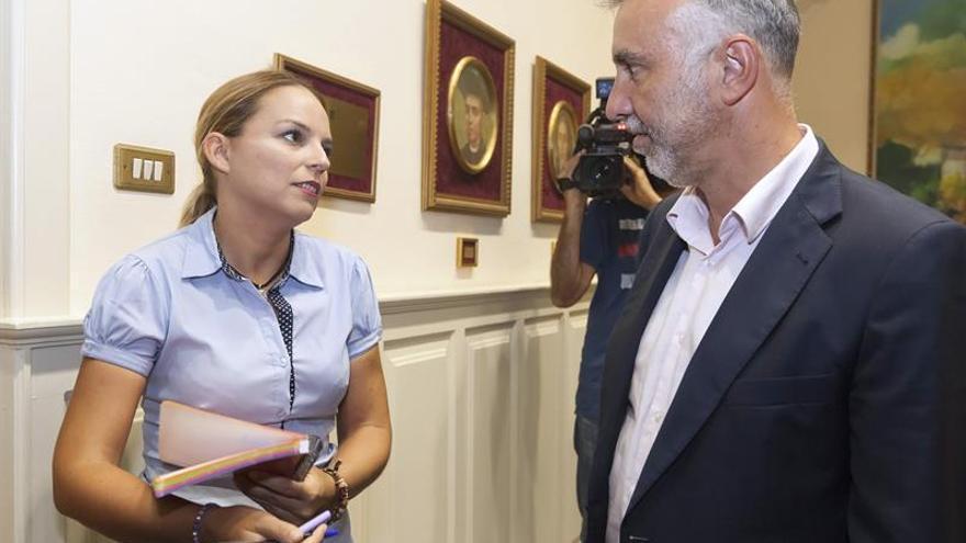 El secretario general del PSOE de Canarias, Ángel Víctor Torres (d), conversa con la secretaria general de Podemos, Noemí Santana