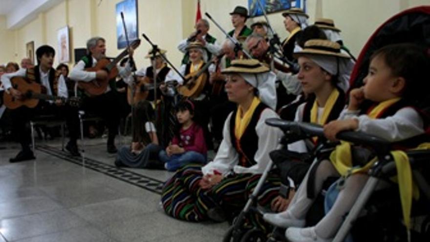 Celebración del Día de la Hispanidad en el Centro Archipiélago Canario de Buenos Aires, en el porteño barrio de Flores. Un bebé asiste en primera fila a la actuación de la rondalla. (A. C.)