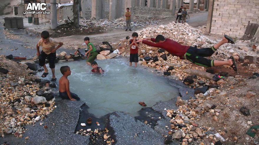 Varios niños sirios en el hoyo provocado por un misil en la zona de Alepo controlada por los rebeldes.
