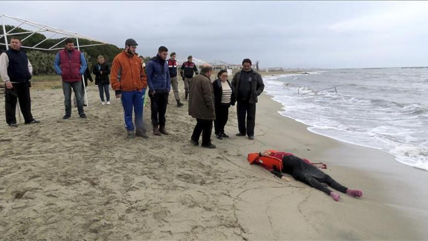 Varias personas observan el cadáver de una mujer, ahogada tras naufragar la embarcación en la que trataba de llegar a Grecia desde la costa de Turquía, en la localidad costera de Ayvalik, en Balikesir (Turquía) este 5 de enero de 2015.