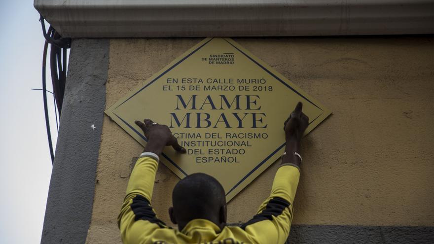 Un hombre coloca una placa simbólica en homenaje a Mame Mbaye.