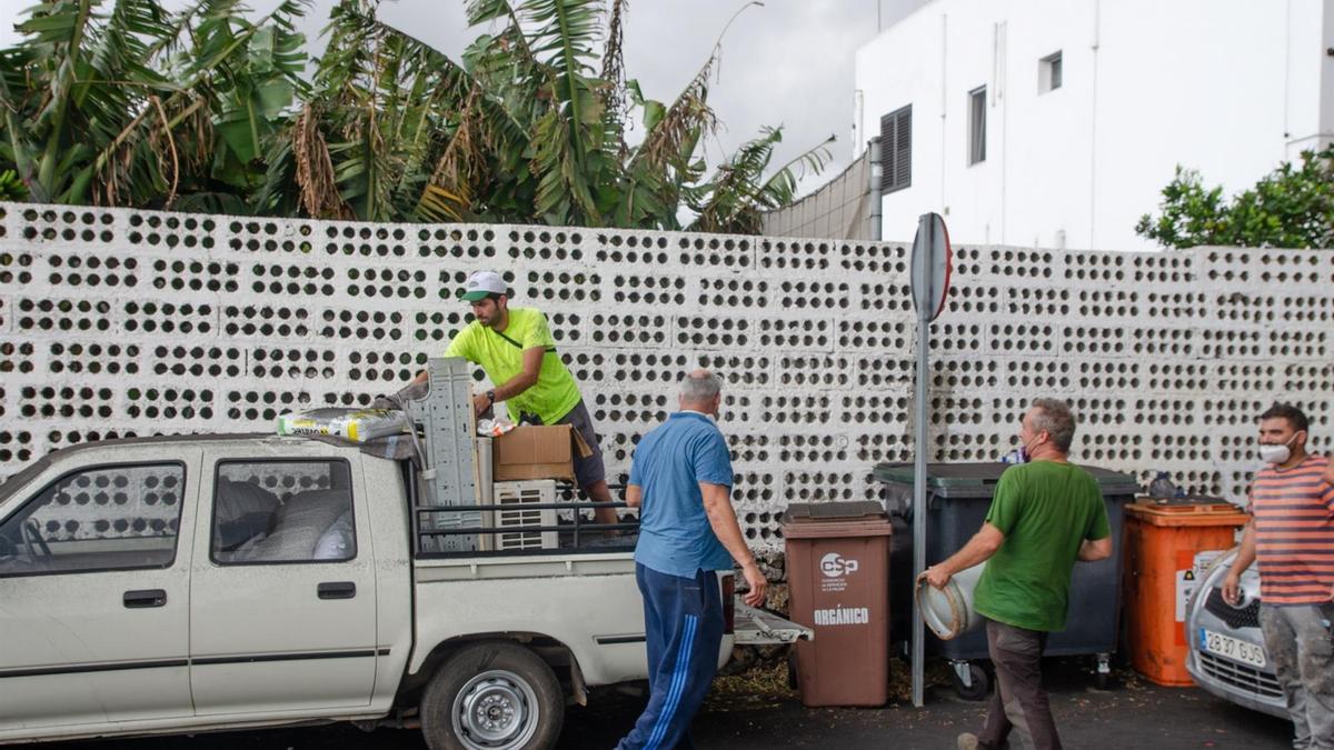 Unos hombres cargan enseres en una camioneta en la localidad de La Laguna. EFE/ Miguel Calero