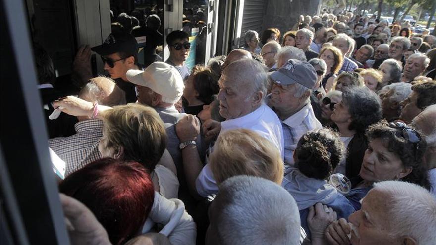 Miles de jubilados griegos hacen colas en los bancos para cobrar parte de sus pensiones